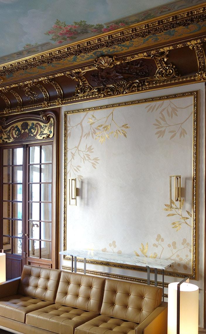 Solène Eloy - Fresquiste - Atelier du Mur - Décors muraux - Fresque motif feuillage doré - Canapé en cuir capitonné - Signatures Singulières Magazine
